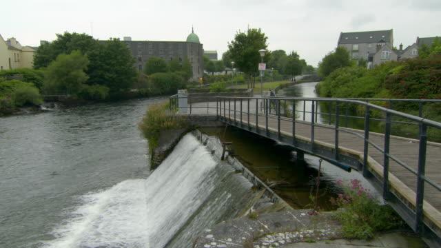 lockdown shot of footbridge over river amidst buildings in town against sky - galway, ireland - riverbank stock videos & royalty-free footage