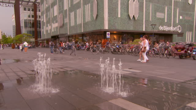 lockdown shot of fountain on footpath against people and shopping mall in city - eindhoven, netherlands - film festival stock videos & royalty-free footage