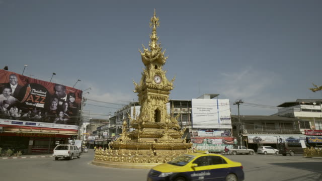 lockdown shot of golden clock tower roundabout with vehicles on street against buildings in city during sunny day - chiang rai, thailand - design element stock videos & royalty-free footage