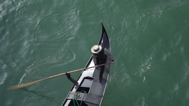 Lockdown shot of gondolier rowing gondola on canal
