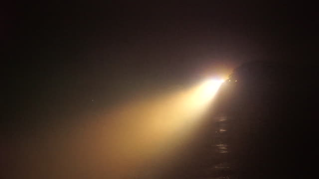 vidéos et rushes de lockdown shot of illuminated lighthouse by sea against sky at night - lighthouse