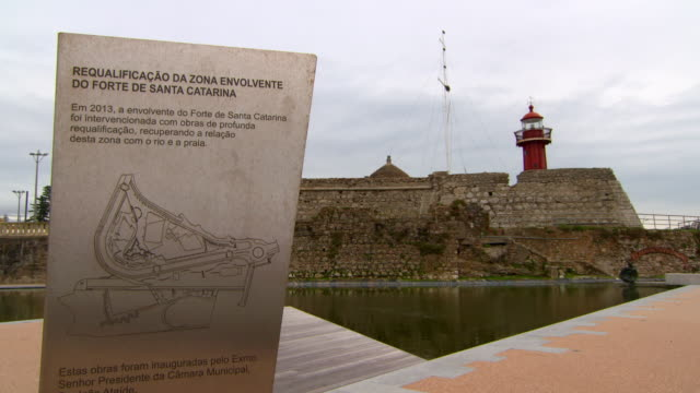 lockdown shot of information sign by pond against sky, lighthouse is in background - figueira da foz, portugal - information sign stock videos & royalty-free footage