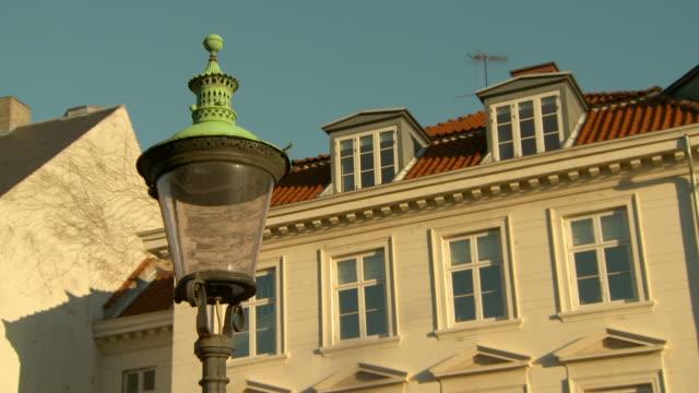lockdown shot of lamp post by residential building in city against sky - copenhagen, denmark - öresundsregionen bildbanksvideor och videomaterial från bakom kulisserna