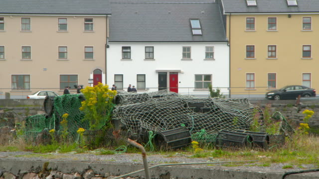 lockdown shot of lobster traps wrapped in fishing nets against buildings - galway, ireland - lobster stock videos & royalty-free footage