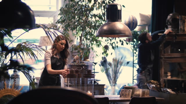 lockdown shot of male and female entrepreneurs arranging decors at flower shop - pendant light stock videos & royalty-free footage