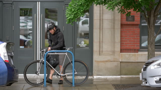 vidéos et rushes de lockdown shot of male commuter parking bicycle and locking it by building in city - casque de vélo