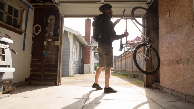vídeos de stock e filmes b-roll de lockdown shot of male commuter taking bicycle from garage - carrying
