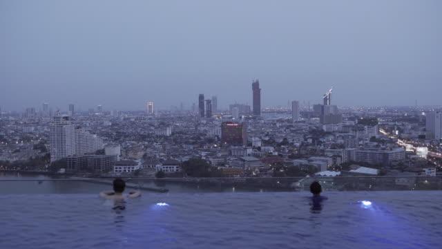 lockdown shot of man and boy enjoying swimming in infinity pool at rooftop overlooking cityscape against sky - bangkok, thailand - インフィニティプール点の映像素材/bロール
