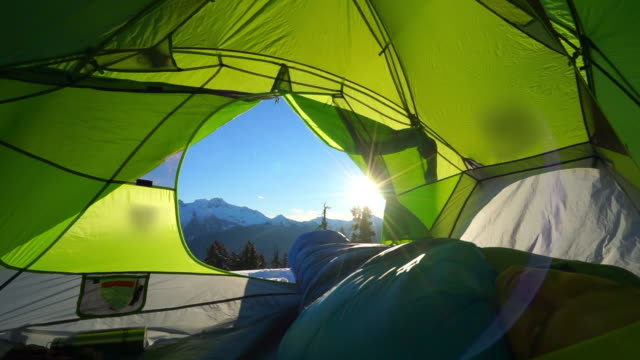 lockdown shot of man sleeping in green tent snowcapped mountains on sunny day - elfin lakes, british columbia - zelt stock-videos und b-roll-filmmaterial
