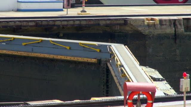 stockvideo's en b-roll-footage met lockdown shot of man walking on panama canal lock - panamakanaal