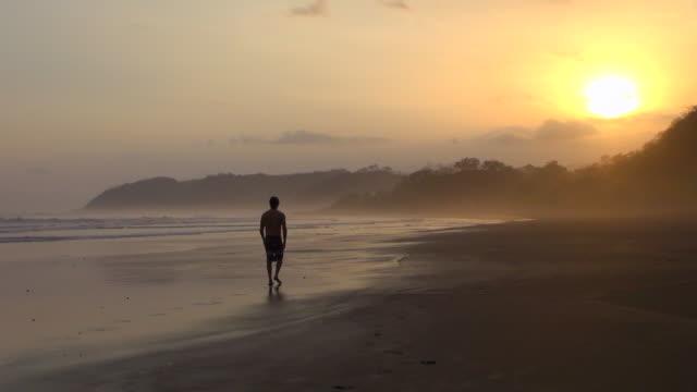 Lockdown Shot of Man Walking on the Beach