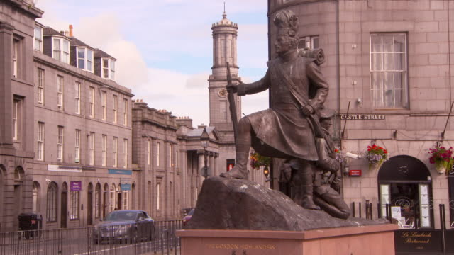 lockdown shot of metallic statue by vehicles on street against buildings in city - aberdeen, scotland - ornate stock videos & royalty-free footage