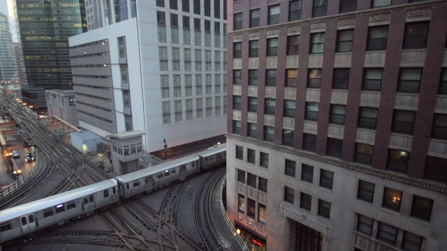 lockdown shot of metro train on bridge amidst buildings in city - chicago, illinois - chicago 'l' stock videos & royalty-free footage