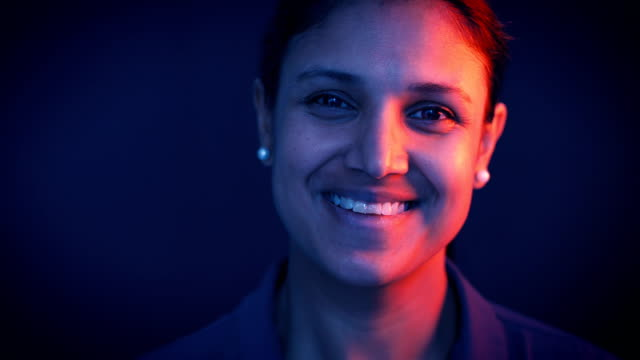 lockdown shot of mid adult businesswoman smiling against gray background - indian subcontinent ethnicity stock videos & royalty-free footage