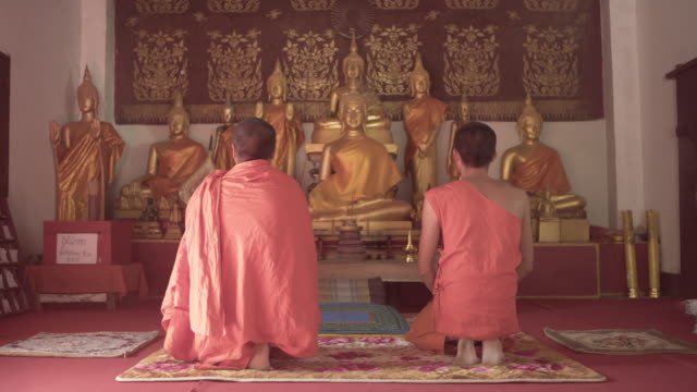 lockdown shot of monks wearing saffron robes while kneeling and praying in front of golden buddha statues in temple - luang prabang, laos - gold dress stock videos & royalty-free footage