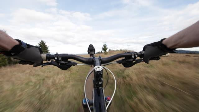 vídeos y material grabado en eventos de stock de pov lockdown shot of mountain bikers riding bicycles at field against cloudy sky - manillar