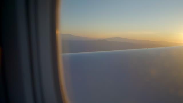 stockvideo's en b-roll-footage met lockdown shot of mountain range seen through airplane window, scenic view of landscape against orange sky - new york city, new york - watervorm