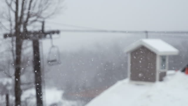 lockdown shot of overhead cable cars and house roof during snowy weather - dacherker stock-videos und b-roll-filmmaterial