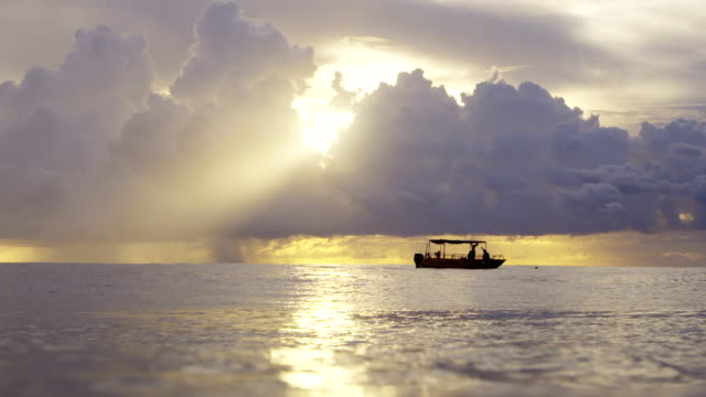 lockdown shot of people in boat on sea against cloudy sky during sunset - tahiti stock videos & royalty-free footage