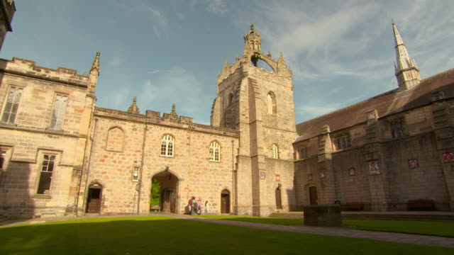 lockdown shot of people walking at famous university in city against sky on sunny day - aberdeen, scotland - pinnacle stock videos & royalty-free footage