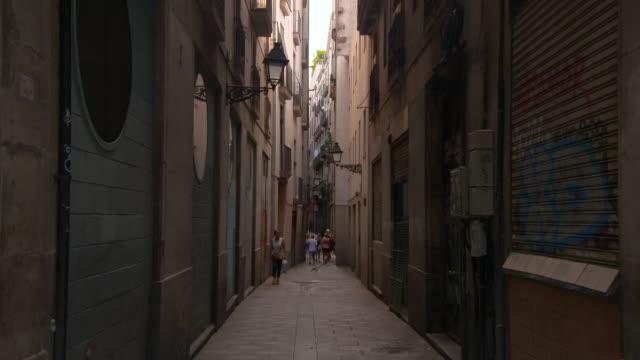 vídeos y material grabado en eventos de stock de lockdown shot of people walking on narrow street amidst buildings - barcelona, spain - contraventana