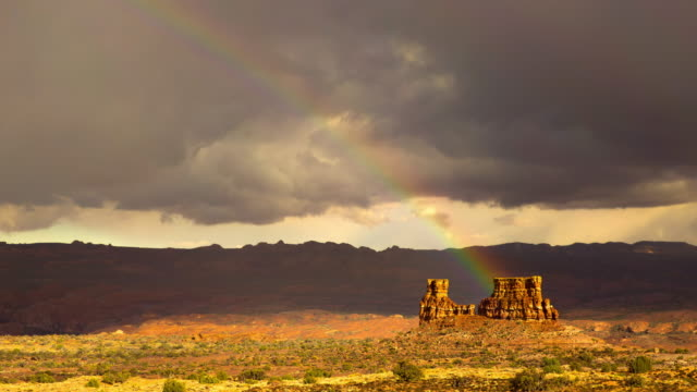 lockdown shot of rainbow over famous three sisters against cloudy sky - arches national park, utah - arches national park stock videos & royalty-free footage