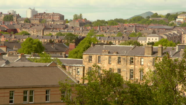 lockdown shot of residential buildings and trees in city against sky on sunny day - glasgow, scotland - glasgow stock videos & royalty-free footage
