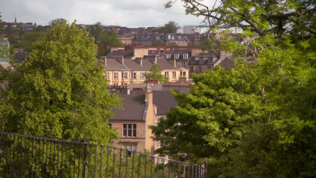 lockdown shot of residential buildings and trees in town against sky on sunny day - glasgow, scotland - スコットランド グラスゴー点の映像素材/bロール