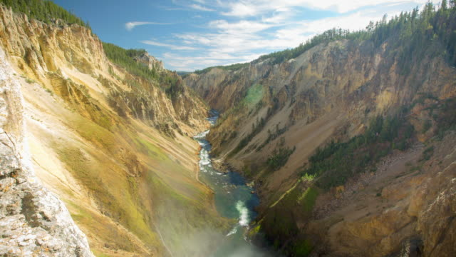 lockdown shot of river flowing amidst rock formations against sky on sunny day - yellowstone national park, wyoming - river yellowstone stock videos & royalty-free footage