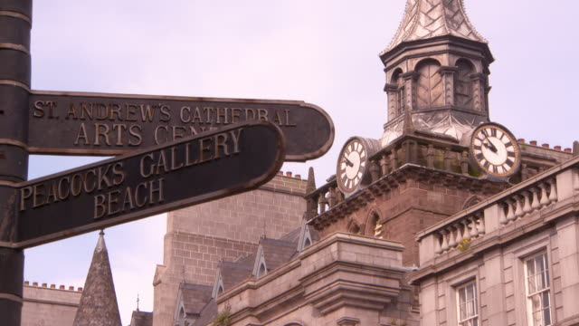 lockdown shot of road sign against famous museum clock tower in city - aberdeen, scotland - western script stock videos & royalty-free footage