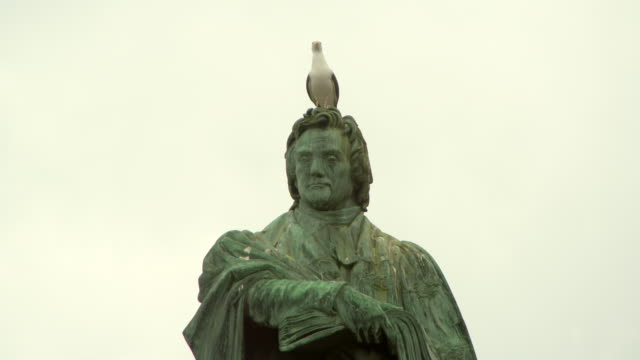 stockvideo's en b-roll-footage met lockdown shot of seagull taking off from thomas chalmers statue in city against sky - edinburgh, scotland - mannelijke gelijkenis