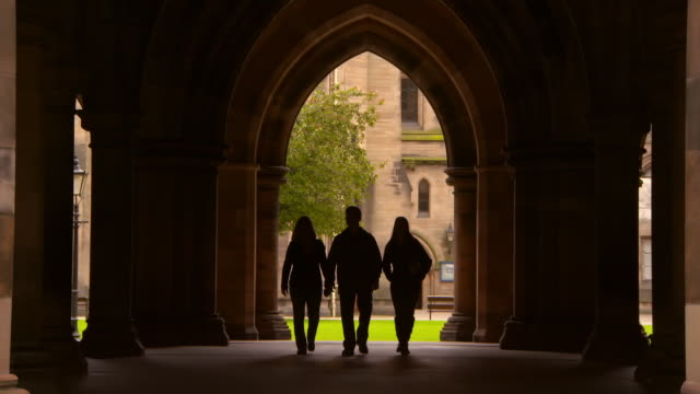 lockdown shot of silhouette people walking in public university archway - glasgow, scotland - religion stock videos & royalty-free footage