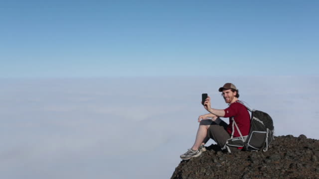 lockdown shot of smiling man with backpack taking selfie through mobile phone while sitting on cliff against sky - remote location phone stock videos & royalty-free footage