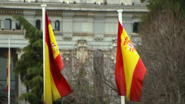 lockdown shot of spanish flags waving against bare trees in city - madrid, portugal - embassy stock videos & royalty-free footage