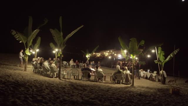 lockdown shot of tourists enjoying camping at illuminated beach against sky during night - luang prabang, laos - film festival stock videos & royalty-free footage