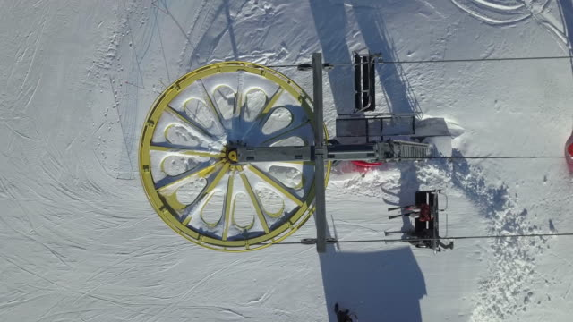 lockdown shot of turning ski lift wheel on snow covered mountain, les sybelles, haute-savoie, france - ski lift stock videos & royalty-free footage