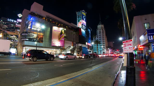 vídeos de stock, filmes e b-roll de lockdown shot of vehicles moving on road in illuminated city, hoardings over buildings against clear sky at night - los angeles, california - time lapse de trânsito