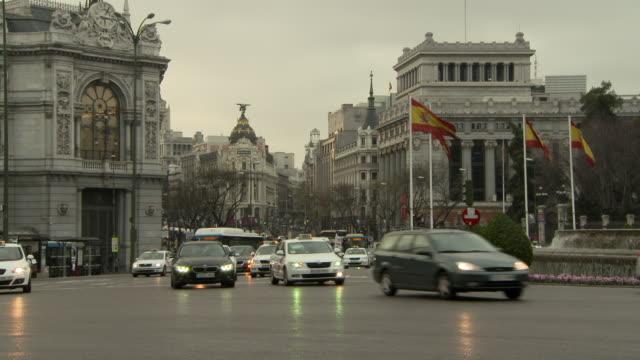 lockdown shot of vehicles moving on street against sky in city during sunset - madrid, portugal - スペイン国旗点の映像素材/bロール