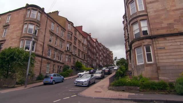 lockdown shot of vehicles on street amidst brown residential buildings in city against sky - glasglow, scotland - western script stock videos & royalty-free footage