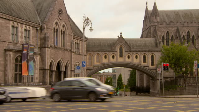 lockdown shot of vehicles on street by museum and cathedral in city against sky - dublin, ireland - natural arch stock videos & royalty-free footage