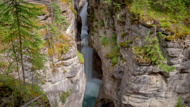 stockvideo's en b-roll-footage met lockdown shot of waterfall through rocky cliffs at maligne canyon in famous national park - jasper national park, canada - jasper national park