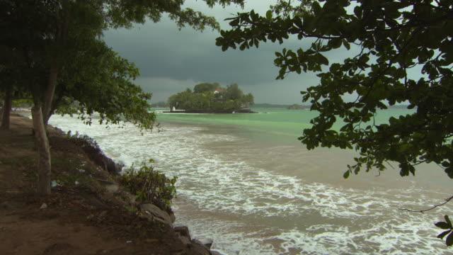 lockdown shot of waves on shore at beach against cloudy sky - arugam bay, sri lanka - zweig stock-videos und b-roll-filmmaterial