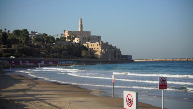lockdown shot of waves splashing on shore at beach by building against sky - jaffa, israel - jaffa stock videos & royalty-free footage