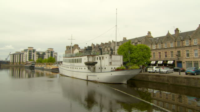 lockdown shot of white ship moored in river canal by buildings against sky - edinburgh, scotland - moored stock videos & royalty-free footage
