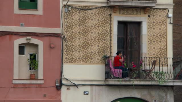 vídeos de stock e filmes b-roll de lockdown shot of woman applying lipstick while sitting in balcony - barcelona, spain - confinamento