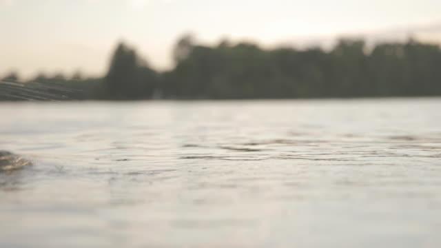 vídeos de stock, filmes e b-roll de lockdown shot of woman swimming in lake during sunset - touca de natação