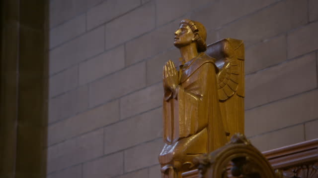 lockdown shot of wooden male angel statue against brick wall at university - glasgow, scotland - statue stock-videos und b-roll-filmmaterial