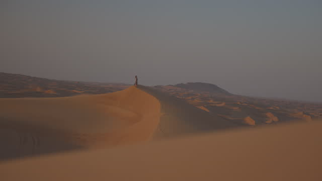 lockdown slow motion shot of woman standing on sand dune in desert during vacation - dubai, united arab emirates - persian gulf stock videos & royalty-free footage