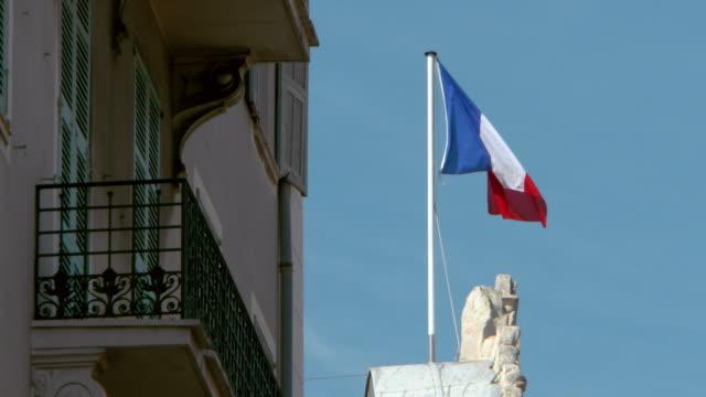 vídeos y material grabado en eventos de stock de lockdown: the french tricolor blowing in the wind in front of a vivid blue sky - detalle arquitectónico exterior
