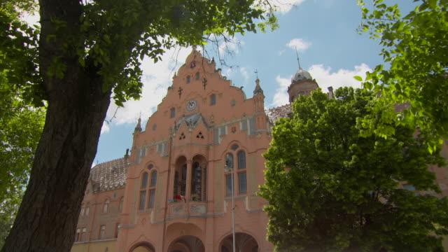 vídeos y material grabado en eventos de stock de lockdown through tree canopy to the top of the fa�ade of town hall in kecskemet - detalle arquitectónico exterior